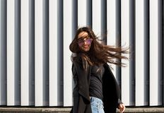 Street portrait of happy young model with hair blowing in wind w. Street portrait of happy young woman with hair blowing in wind walking at the street stock image