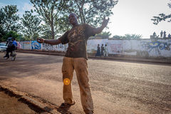 Street portrait. Jinja, Uganda -September 2015 - An excited homeless man posses for a photo. The man says he calls the streets of this neighborhood his home Royalty Free Stock Photography