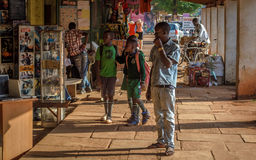 Street portrait. Jinja, Uganda -September 2015 - School going children window shop on their way back home. The streets of this town are filled with school-going Stock Images