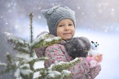 Street portrait of the little girl in the cat hat with a snowman enjoying first snow