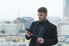 Street portrait of a man with a beard who smokes a cigarette and uses a smartphone on the street background stock photos