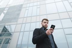 Street portrait of a man in a suit from a lower angle against the backdrop of urban modern architecture. A serious young man with a beard while walking is Royalty Free Stock Photos