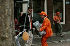 Street portrait of men in orange, crazy look, preparations for King`s Day festivity in the Netherlands Royalty Free Stock Image