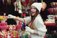 Street portrait of smiling beautiful young woman buying candy on the festive Christmas fair. Lady wearing classic Royalty Free Stock Image