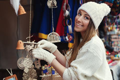 Street portrait of smiling beautiful young woman buying decorations on the festive Christmas fair. Lady wearing classic Royalty Free Stock Photos