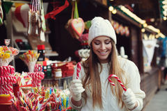 Street portrait of smiling beautiful young woman choosing candy canes on the festive Christmas fair. Lady wearing Stock Photography