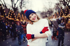 Street portrait of smiling beautiful young woman on the festive Christmas fair. Lady wearing classic stylish winter Royalty Free Stock Image