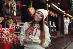 Street portrait of smiling beautiful young woman holding candy canes and looking at camera. Lady wearing classic stilish. Winter knitted clothes. Festive Stock Image