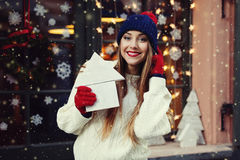 Street portrait of smiling beautiful young woman holding wooden toy house. Lady wearing stylish classic winter knitted Royalty Free Stock Photo