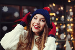 Street portrait of smiling beautiful young woman wearing stylish classic winter knitted clothes. Model looking at camera Stock Photography