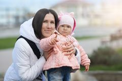 Street portrait of the smiling mother with her serious daughter. Mood difference Royalty Free Stock Photo