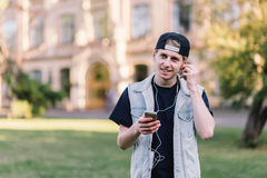Street portrait of a smiling student listening to music in headphones on campus background. Student Life. Happy young man holding books while standing Stock Photo