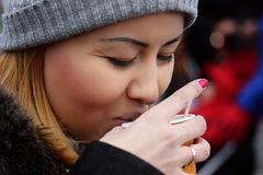 Street portrait of a young beautiful caucasian/asian woman in warm clothes. She drinks hot tea from a plastic cup to keep warm. royalty free stock images