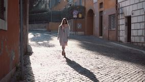 Street portrait of young beautiful fashionable woman walking at the old city. Girl looking around, exploring the town. Street portrait of young beautiful stock video footage