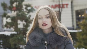 Street portrait of young beautiful woman posing at camera. In winter day. Slowly stock footage