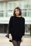 Street portrait of young elegant brunette hipster woman in black blouse and skirt against a blurred city background Royalty Free Stock Image
