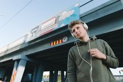 Street portrait of a young man listening to music in headphones at the background of the bridge. Stock Images