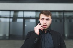 A street portrait of a young serious man with a beard that communicates on a mobile phone against a dark wall Royalty Free Stock Photo
