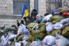 Street protests in Kiev, a barricade with revolutionaries. The rebels in masks on the barricade are waiting for the attack royalty free stock images