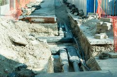 Street reconstruction site of district heating system pipeline with ground excavation end replacement of old pipes with new ones. Street reconstruction site of stock image