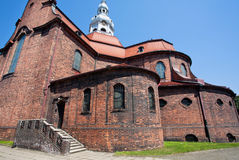 Street with red brick walls of the old catholic church Stock Photo