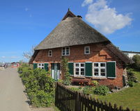 Street and reed roofed house in Stahlbrode in Mecklenburg-Vorpommern. The building is a listed monument.  stock photography