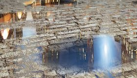 Street Reflections. City buildings reflecting in puddles on a brick street (3d render royalty free illustration