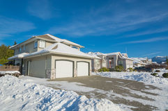 Street of residential houses on winter sunny day. Double garage of big luxury house with driveway and front yard in snow. Street of residential houses on winter Stock Images