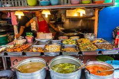 Street restaurant Bangkok Thailand. Bangkok, Thailand - April 12, 2019: Woman cooking and selling a wide variety of cheap thai meals in a street restaurant in stock photography