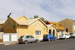 Street restaurant hotel, Keetmanshoop, Namibia. Street with restaurant and hotel accommodation signs, yellow colonial German buildings and parked cars in Royalty Free Stock Photography