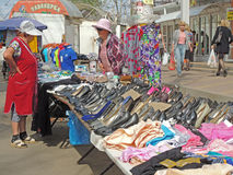 Street retail of clothing and ladies shoes. Street sale of clothing and ladies shoes. Street retail saleswoman talk on the city sidewalk royalty free stock photos