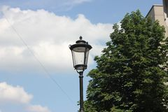 Street retro lamp against the blue sky. Avenue in a big city with light clouds and a lantern, summer green streets and a lantern in daylight on a hot day royalty free stock image