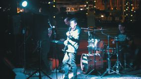 Street rock band plays guitars, drums and sing songs at night stock video footage