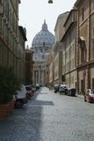 Street of Rome with St. Peter in the background. Local street in Rome with the dome of the St. Peter Cathedral in the background Stock Photography