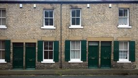 Street with a row of typical british old terraced houses with green doors and window shutters in durham england royalty free stock photo