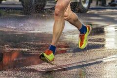 Street runner runs on wet street Royalty Free Stock Photos