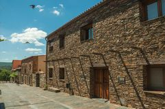Street with rustic houses and stone walls with plants royalty free stock image