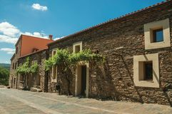 Street with rustic houses and stone walls with plants royalty free stock images