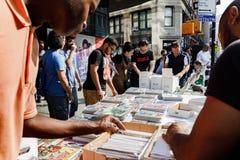 Street sale of comics in Manhattan in New York City. NEW YORK, USA - Sep 16, 2017: Street sale of comics in Manhattan in New York City. Young men choose comics Stock Photo
