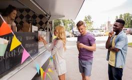 Happy customers queue at food truck. Street sale and people concept - happy customers queue at food truck stock image