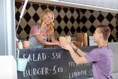 Saleswoman at food truck serving male customer. Street sale and people concept - happy young saleswoman at food truck serving male customer stock photography