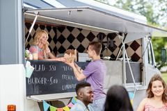 Saleswoman at food truck serving male customer. Street sale and people concept - happy young saleswoman at food truck serving male customer stock photos