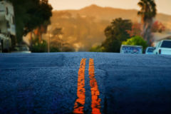 Street Scene. Orange road surface markings with landscape in the background Stock Image