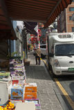 Street scene in China Town, Incheon, South Korea. A market stall laid out in Chinatown, Incheon, South Korea, with a van parked nearby and a man walking up the Stock Photos