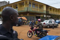 Street scene in the city of Bissau with people crossing a street and vendors, in Guinea-Bissau, West Africa stock photo