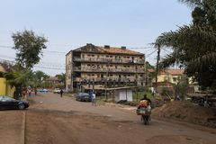 Street scene in the city of Bissau with people walking in a stret and a crumbling building on the background, in Guinea-Bissau stock photography
