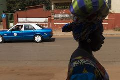 Street scene in the city of Bissau with the silhouette of a woman and a taxi on the background, in Guinea-Bissau. Bissau, Republic of Guinea-Bissau - January 30 royalty free stock images