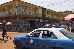 Street scene in the city of Bissau with a taxi and people crossing a dirt road, in Guinea Bissau Stock Photo