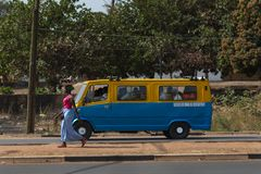 Street scene in the city of Bissau with a woman carrying a tray on her head and a public bus toca toca in Guinea-Bissau. Bissau, Republic of Guinea-Bissau Royalty Free Stock Photo