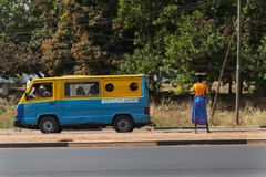 Street scene in the city of Bissau with a woman carrying a tray on her head and a public bus toca toca in Guinea-Bissau. Bissau, Republic of Guinea-Bissau Stock Photography